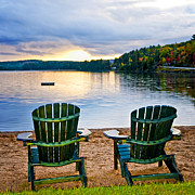 Lake Posters - Wooden chairs at sunset on beach Poster by Elena Elisseeva