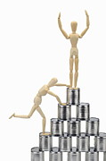 Can Prints - Wooden mannequin climbing tin cans pyramid Print by Sami Sarkis