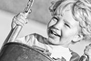 Enjoying Framed Prints - Young Boy Smiling Swinging In A Swing Framed Print by Robert Postma