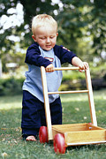 Child Care Posters - Young Boy Taking His First Steps Poster by Ian Boddy