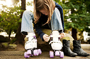 Girl Looking Down Posters - Young Girl Putting On Roller Skates Poster by Cavan Images
