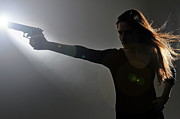 Aiming Prints - Young woman holding gun Print by Sami Sarkis