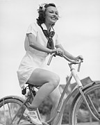 Young Adult Framed Prints - Young Woman Riding Bicycle, (b&w), Low Angle View Framed Print by George Marks