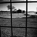 looking out through door window to snow covered scene in small rural village of Forget Saskatchewan  by Joe Fox