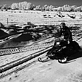 man on snowmobile crossing frozen fields in rural Forget Saskatchewan Canada by Joe Fox