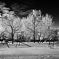 empty childrens playground with hoar frost covered trees on street in small rural village of Forget  by Joe Fox