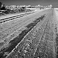 frozen salt and grit covered rural small road in Forget Saskatchewan Canada by Joe Fox