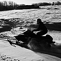 man on snowmobile crossing frozen fields in rural Forget Saskatchewan by Joe Fox