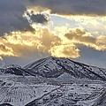 Stormy Sunset Over Snow Capped Mountains by Tracie Kaska