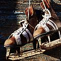 Vintage Pair Of Mens  Ice Skates Hanging On A Wooden Wall With C by Mikhail Olykaynen