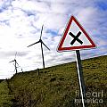 Wind Turbines On The Edge Of A Field With A Road Sign In Foreground. by Bernard Jaubert