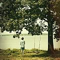 Young boy looking out at the water under a big tree Print by Sandra Cunningham