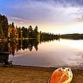 Lake sunset with canoe on beach Print by Elena Elisseeva