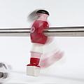 A Foosball Figurine Kicking A Soccer Ball, Blurred Motion by Caspar Benson