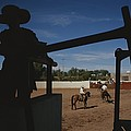 A Silhouetted Cowboy Watches Riders by Raul Touzon