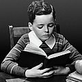 Boy Reading Book At Desk by George Marks