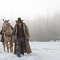 Cowboy Walking His Horse And Holding A Shotgun by Thomas Kokta