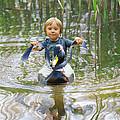 Cute Tiny Boy Riding A Duck by Jaroslaw Grudzinski