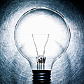 Light Bulb On Stainless Steel Background. by Ballyscanlon