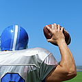 Rear View Of A Football Player Throwing A Football by Stockbyte