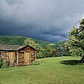 Storm Clouds Form Above A Log Cabin by Raymond Gehman