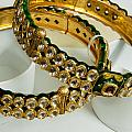 Two Green And Gold Bangles On Top Of Each Other by Ashish Agarwal