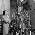 Woman Assisting Man Placing Star On Top Of Christmas Tree, (b&w) by George Marks