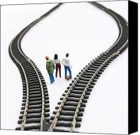 Pensive Canvas Prints - Figurines between two tracks leading into different directions symbolic image for making decisions. Canvas Print by Bernard Jaubert