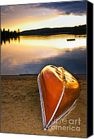 Tranquil Canvas Prints - Lake sunset with canoe on beach Canvas Print by Elena Elisseeva