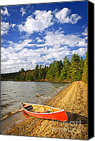 Tranquil Canvas Prints - Red canoe on lake shore Canvas Print by Elena Elisseeva