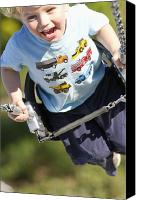 T-shirt Canvas Prints - Young Boy Smiling Swinging In A Swing Canvas Print by Robert Postma