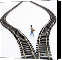 Pensive Canvas Prints - Figurine between two tracks leading into different directions symbolic image for making decisions. Canvas Print by Bernard Jaubert