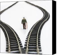 Consider Canvas Prints - Figurine between two tracks leading into different directions symbolic image for making decisions. Canvas Print by Bernard Jaubert