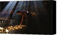 Tibetan Buddhism Canvas Prints - A Buddhist Monk Lights Devotional Lamps Canvas Print by Maria Stenzel