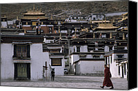 Tibetan Buddhism Canvas Prints - A Monk Walks Past A Small Village Canvas Print by Jimmy Chin