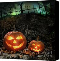 Evil Canvas Prints - Halloween pumpkins on rocks  at night Canvas Print by Sandra Cunningham