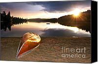 Leisure Canvas Prints - Lake sunset with canoe on beach Canvas Print by Elena Elisseeva