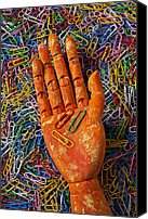 Fingers Photo Canvas Prints - Orange wooden hand holding paperclips Canvas Print by Garry Gay