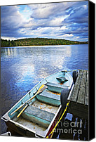 Tranquil Canvas Prints - Rowboat docked on lake Canvas Print by Elena Elisseeva