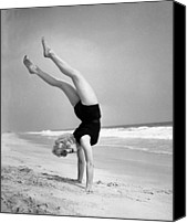 One Piece Swimsuit Canvas Prints - Woman Does Handstand On The Beach (b&w) Canvas Print by Hulton Archive