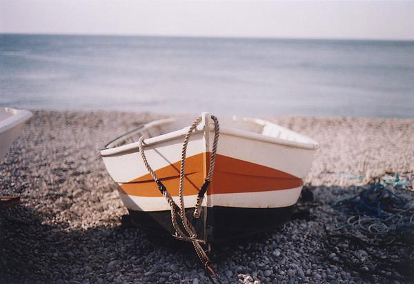 Boat On Pebble Beach Print by Deborah Leca