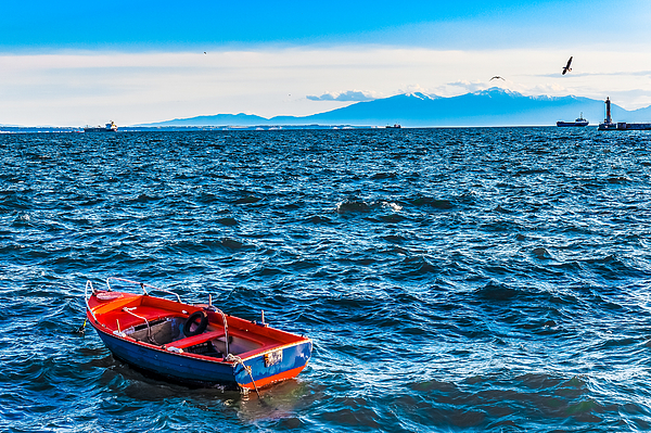 Empty fishing boat in the wavy sea with mountains and for 21 iceboat terrace for sale