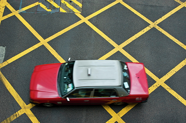 Red Taxi Cab Driving Over Yellow Lines In Hong Kong Print by Sami Sarkis