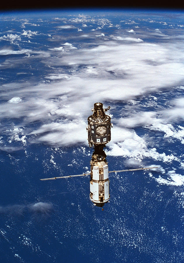 Vertical Photograph - A Satellite Orbiting Above The Earth by Stockbyte