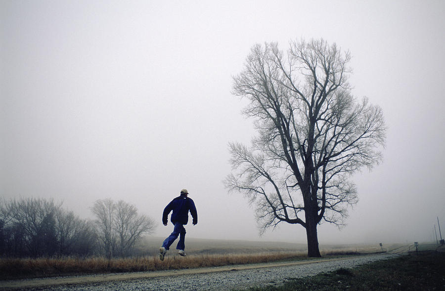 A Man Leaps In The Air On A Gravel Road Photograph