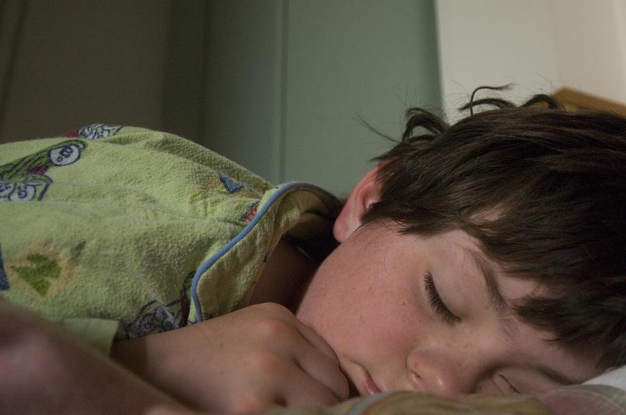 A Young Boy Sleeps In Green Pajamas Photograph