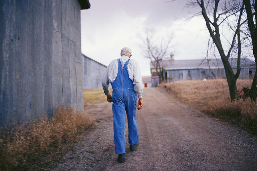 An Elderly Farmer In Overalls Walks Photograph