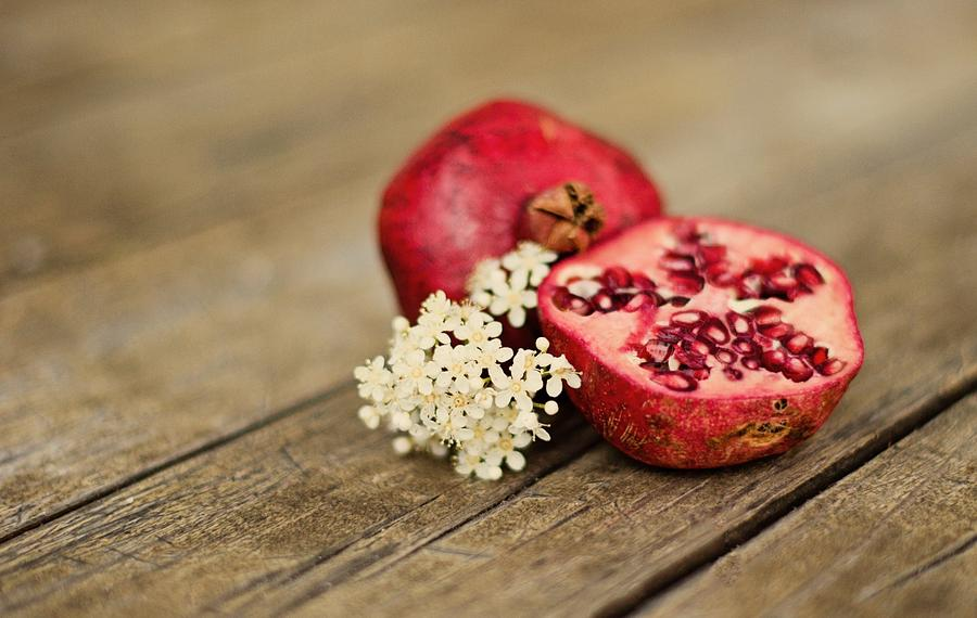 Pomegranate And Flowers On Tabletop Photograph