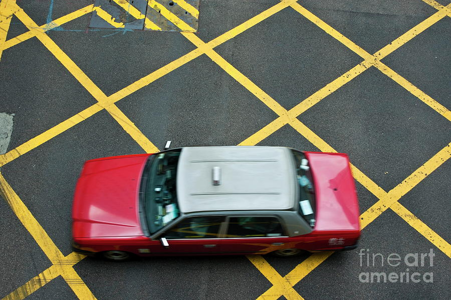 Red Taxi Cab Driving Over Yellow Lines In Hong Kong Photograph