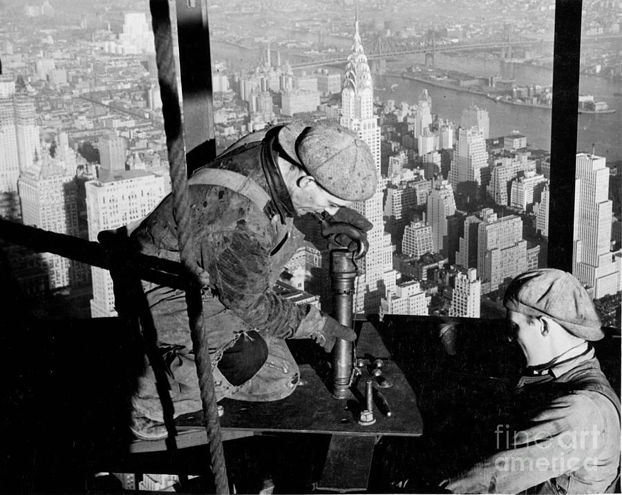 Riveters; Riveting; Male; Work; Labour; Workers; Working; Labourers; Construction; Building; History; Historical; Landmark; Skyscraper; High-rise; Empire State Building; 1930s; 30s; Thirties; Us; Usa; America; American; United States; High; Challenge; Risk; Danger; Courage; Bravery; Heights; Achievement; Scale; Teamwork; Chrysler Building; Aerial View; New York; Manhattan; Architecture; Urban; City; Cityscape; Dramatic; Builder; Builders; Scenic; Concentration; Black And White Photograph; B/w Photo; Photography Photograph - Riveters On The Empire State Building by LW Hine
